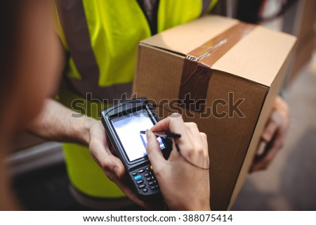 Woman signing on device to delivery parcel by van - stock photo