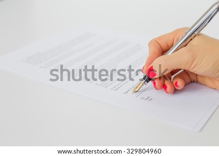 Woman signing papers - stock photo