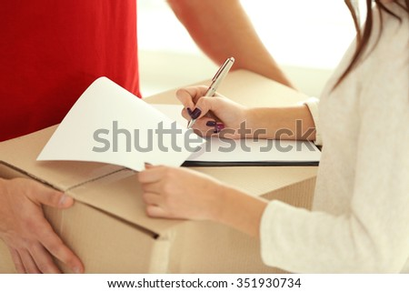 Woman signing receipt of delivery package, close up - stock photo