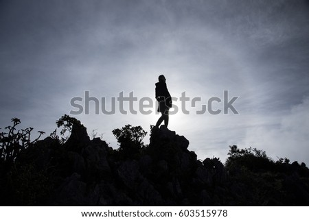 Woman Silhouette at sunrise on rock