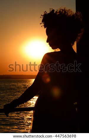 Woman  silhouette at  sunset on beach