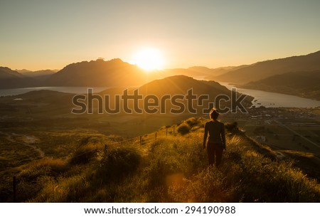 Woman silhouette at sunset on the mountain. New Zealand - stock photo