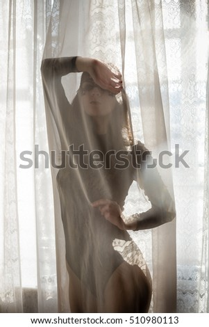 Woman silhouette behind transparent curtain on light window sunny abstract background