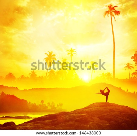 Woman silhouette doing Yoga in tropics near the sea at sunset in India - stock photo