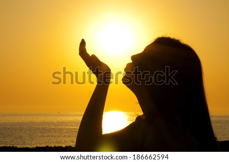 Woman silhouette kiss sun - stock photo