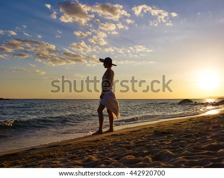 Woman silhouette on beach sunset