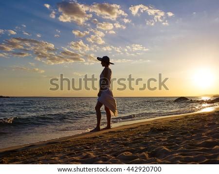 Woman silhouette on beach sunset - stock photo