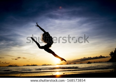 woman silhouette on sunset beach background