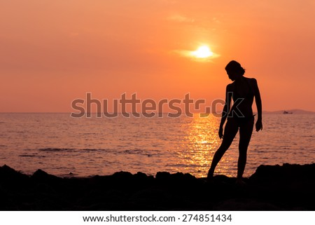 Woman silhouette on sunset sea background back lit