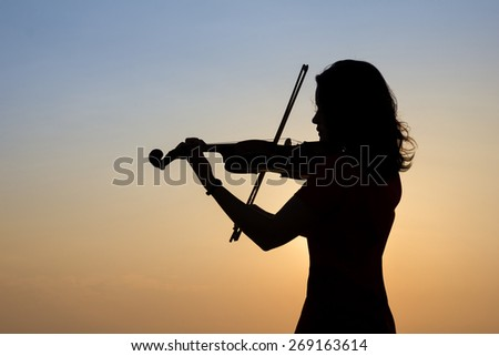 Woman silhouette playing violin in sunrise sky background. - stock photo
