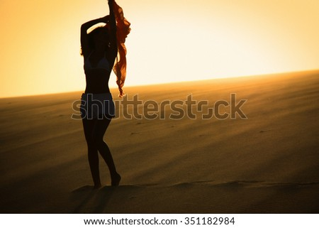 Woman silhouette with scarf in the hand in sunset on sand dune/ health nice woman body/sunset shoots woman