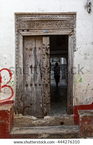 woman silhouetted in the arch of an old square zanzibar arabic doorway