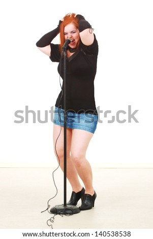 Woman singing into a microphone - stock photo
