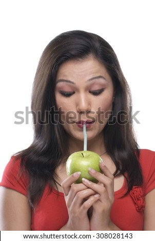 Woman sipping juice from an apple