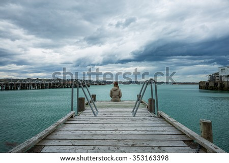 woman sit alone at the edge of the bridge - stock photo