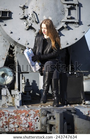 Woman sit on rusty train front with map - stock photo