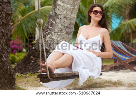 woman sit on swing among palm trees