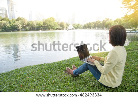 Woman sit to use silver laptop at parks and building in the city with gold light, Bangkok Thailand