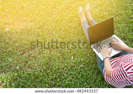 Woman sit to use silver laptop at parks in the city with gold light, Bangkok Thailand
