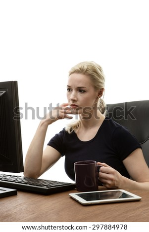 woman siting at her desk working and drink from a cup  - stock photo