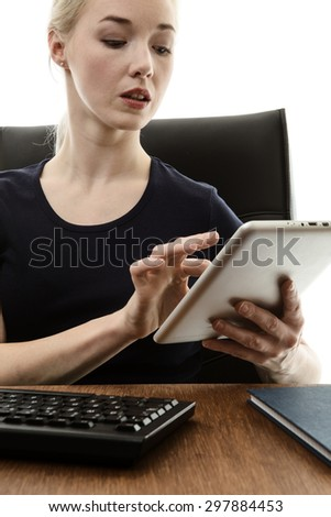 woman siting at her desk working using a tablet