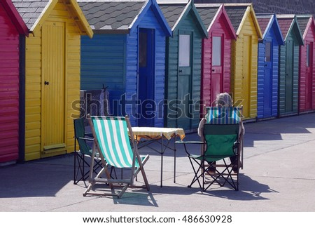 Woman sits in chair in front of row of beach huts