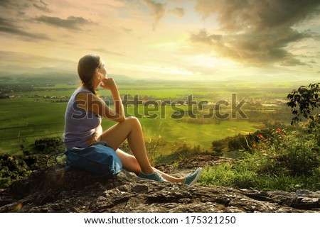 Woman sits on edge of cliff and looking at sun valley and mountains - stock photo