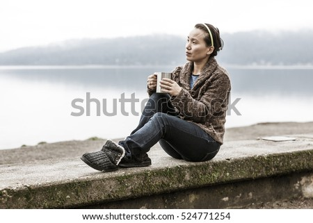Woman sits on ledge by lake.