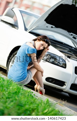 Woman sits on the grass near her broken car with the opened hood waiting for assistance