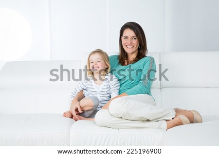 woman sits on the sofa and hugs her little child