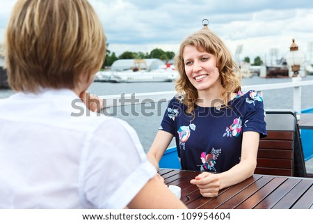Woman sitting against girlfriend at cafe table - stock photo