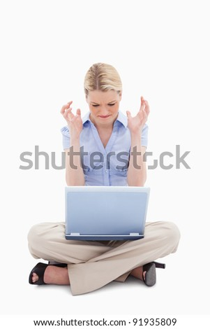 Woman sitting and angry about her laptop against a white background - stock photo
