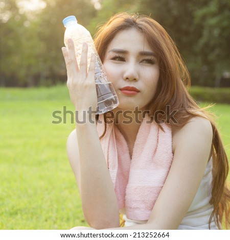 Woman Sitting and holding a bottle of water. Sitting on grass in the park after jogging. In the evening