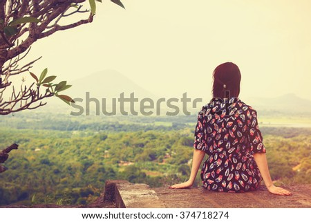 Woman sitting and looking on the landscape  - stock photo