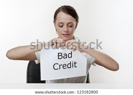 woman sitting at a desk about to get rid of her bad credit history - stock photo