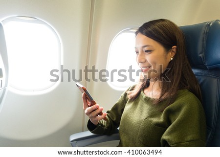 Woman sitting at airplane and looking to mobil phone - stock photo