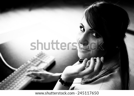 Woman sitting at helpdesk with keyboard closeup photo