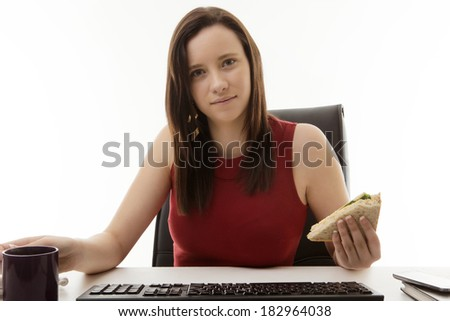 woman sitting at her desk in the office eating a sandwich as well as working on the go