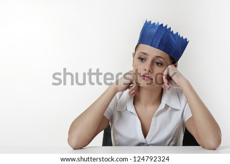 woman sitting at her desk not having a good time wearing a paper hat from a christmas cracker - stock photo