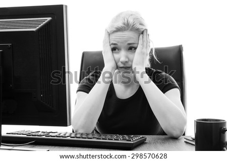 woman sitting at her desk with her head in her hands stressed out - stock photo