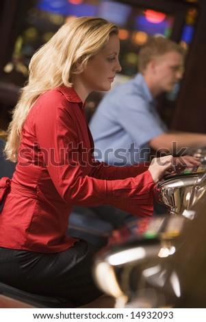 Woman sitting at slot machine in casino parlour - stock photo