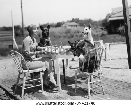 Woman sitting at table outside with three dogs - stock photo