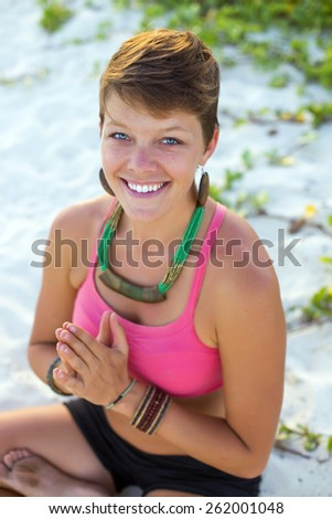 Woman sitting at the beach on a meditation pose - stock photo
