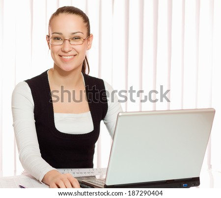 Woman sitting at the desk with laptop - stock photo
