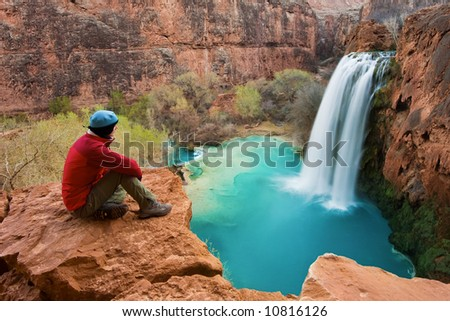 Woman sitting at the edge of a cliff watching Havasu Falls drop into it's turquoise pool. Havasu Canyon, Arizona. Havsupai Reservation.