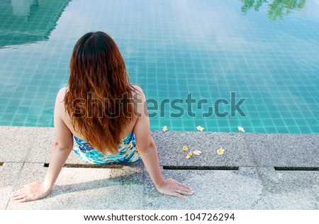 Woman sitting at the Edge of a Swimming Pool - stock photo