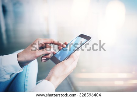 Woman sitting at the floor and touching screen of her smartphone - stock photo