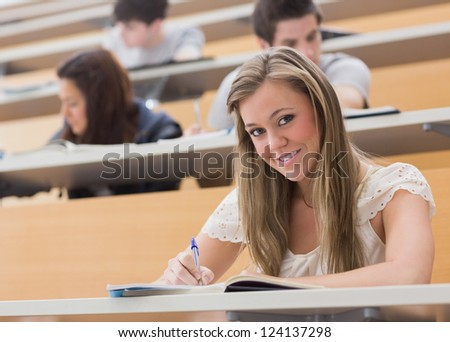 Woman sitting at the lecture hall while smiling and writing notes - stock photo