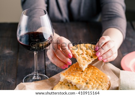 woman sitting at the table enjoys a bead and a glass of red wine