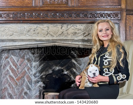 Woman sitting by a fireplace with a dog puppy in luxury interior